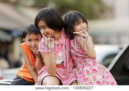 BANGKOK, THAILAND, JANUARY 3, 2012 : A group of kids sitting on a car's roof is posing in a street of Bangkok, Thailand.