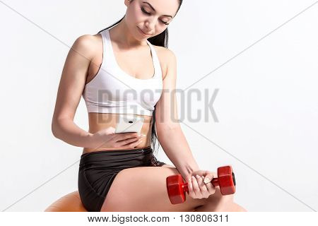 tired young fitness woman resting and sitting on fitball after sport with phone