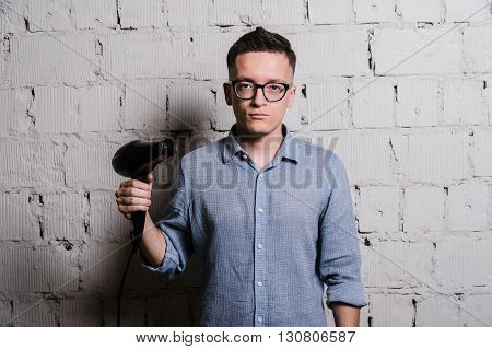 Male stylish hairdresser holding a blow dryer and shooting over grey brick wall