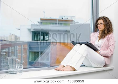 Young creative businesswoman sitting at office window and working on laptop computer.