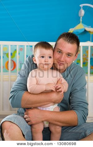 Young father sitting on floor and cuddling baby boy ( 1 year old ) at home in children's room, smiling.