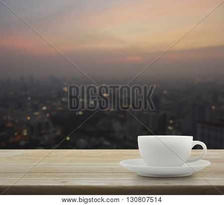 White cup on wooden over blurred aerial view of cityscape on warm light sundown