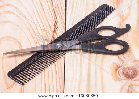 scissors with comb lying on a light wooden table.