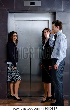 Three businesspeople waiting for the elvator and talking at office lobby.