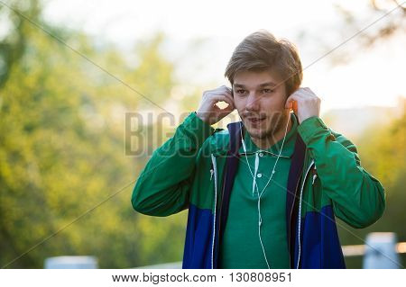 young stylish man listening to music in the city