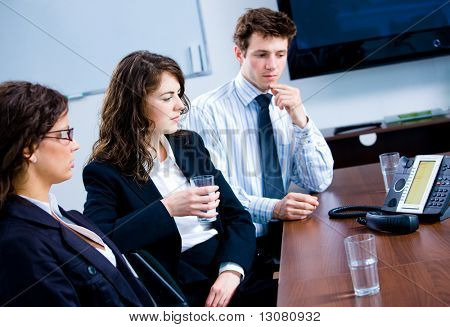 Businesspeople sitting on meeting at office listening phone during a conference call.