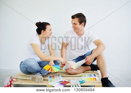 Laughing boy and girl sitting on a wooden pallet in an empty white room. They choose the catalog of paint color.