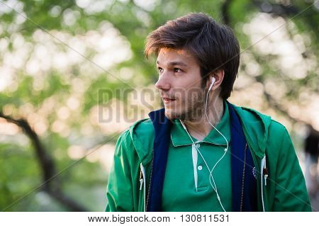 young stylish man standing and listening to music in the city