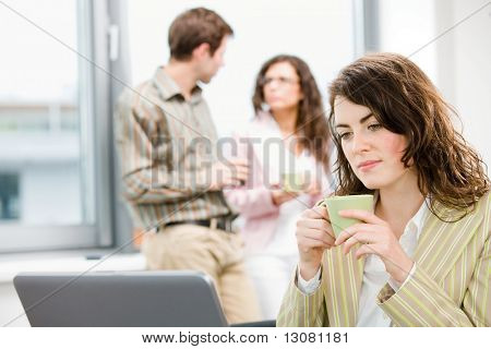 Team of young successful businesspeople having break and drinking coffee at office, businesswoman working on laptop computer in front.