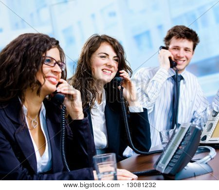 Happy team of customer service operators calling on phone.