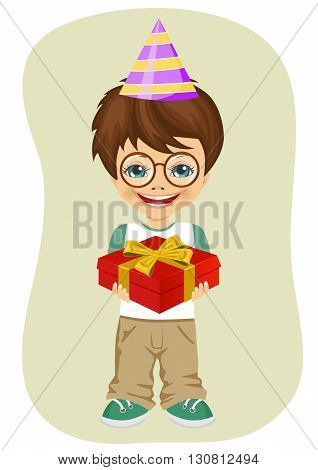 Young nerd boy with party hat holding birthday gift on green background
