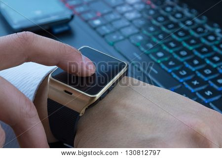 Business Man Using His Smartwatch App Near Computer Pc Keyboard And Smartphone On Daily Light