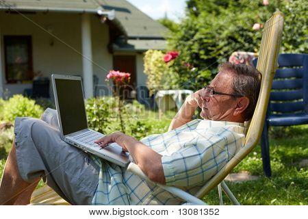 Hombre senior sano es su setenta ancianos sentados al aire libre en el jardín en casa y usando la computadora portátil para