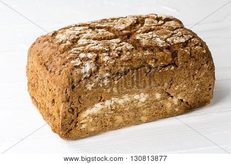 Whole farmers bread on white wooden background.