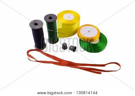 macro green and blue threads on reels an iron needle yellow orange green and red tapes thimbles all for sewing and needlework isolate on a white background