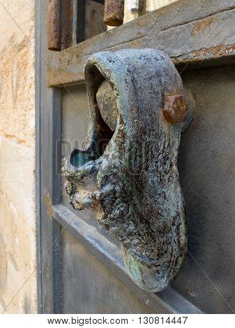 Antique door knocker in the form of a boot on old metal door. Photo taken in Jaffa Israel.