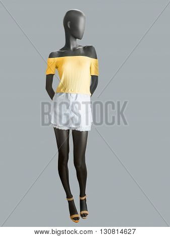 Female mannequin dressed in white skirt and yellow top over grey background