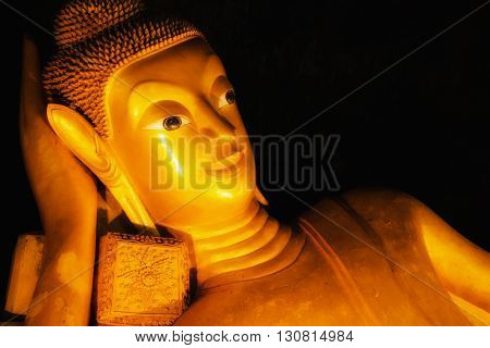 Reclining Buddha gold statue face in black background
