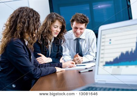 Happy young businesspeople having meeting in board room. Graph showing progress on laptop screen.