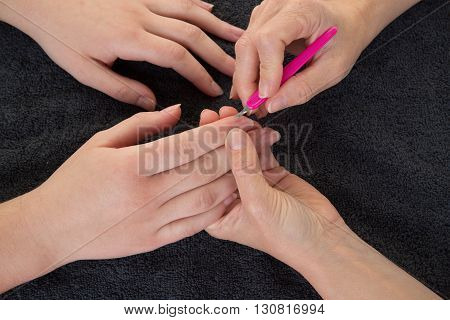 Woman In Nail Salon Receiving A Manicure By Female Beautician