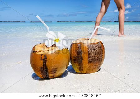 Two coconut cocktails on white sand beach and woman legs at background. Vacation and travel concept