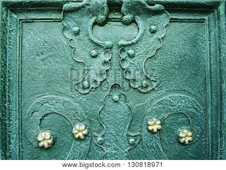 A part of old decorated wrought iron doors. Curved design elements on dark green metal door. Architectural metal background with decorative elements.