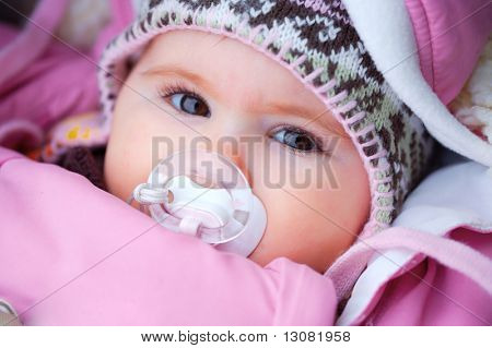 A few months old baby outdoor in warm clothes in a cold winter day.