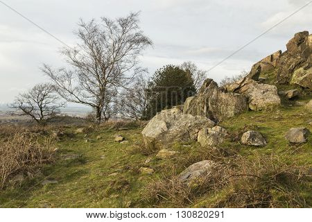 An image of a rocky outcrop and a selection of trees set in the beautiful countryside of Beacon Hill Leicestershire England UK.