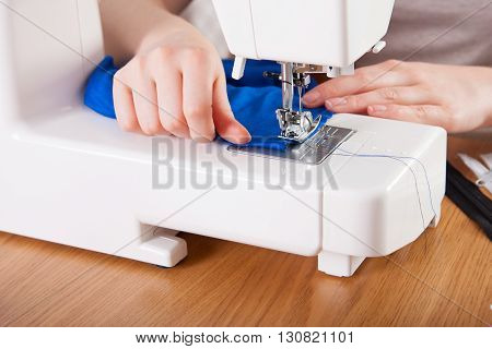 Young Woman Sewing Fabric