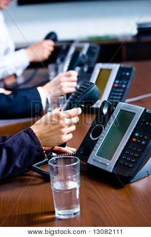 Close-up of hands holding landline phone recievers at customer service office.