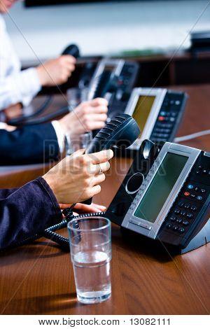 Close-up de mãos segurando o telefone fixo telefone receptores no escritório de serviço ao cliente.