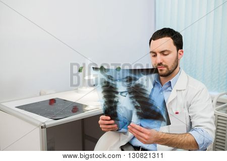 Health and mood. Serious Doctor talking to patient and keeps chest X-ray in hands while sitting at a table in the hospital. H