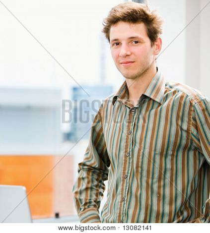 Portrait of a happy young casual businessman at office, smiling.