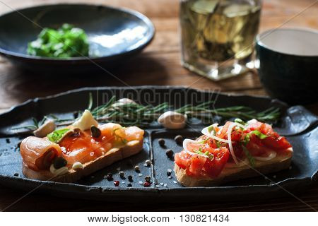 Sandwiches with smoked salmon and tomato on black plate close up. Focus on foreground. Bruschetta with seafood and tomatos, served on wooden background