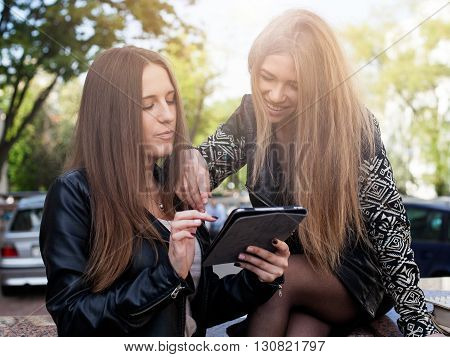 Close up two young women in the city are looking at the the screen of a tablet and smiling