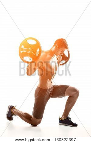 Muscular mighty man standing on knee and holding barbell over his head. Isolated on white background. Whith solar flare