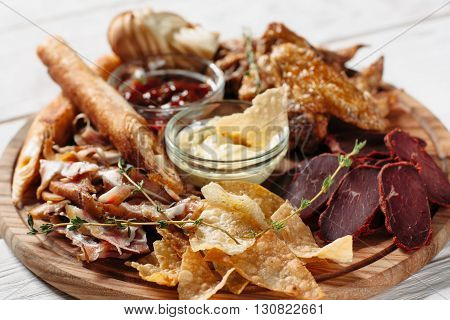 Beer snacks plate, red and yellow sauces on wooden board. Meat, cheese and chips on white background. Closeup of beer snacks set