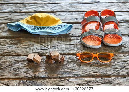 Hat, sandal, sunglasses wooden bricks on wood background, summer concept