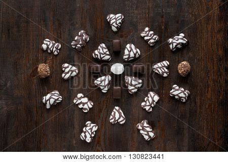 Chocolate candies set on dark wooden background. Different kinds of chocolate candies. Flat lay. Closeup. Figure composition
