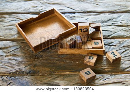 Wooden cubes with numbers on wooden background