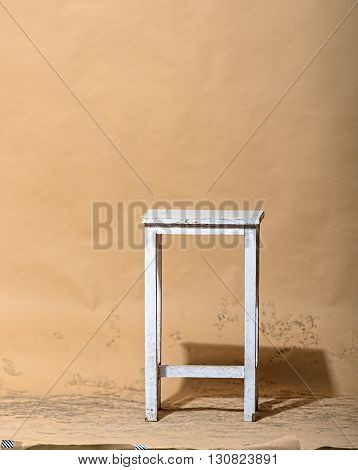 White stool in studio on light brown background with shadows