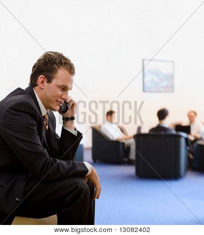 Kaufmann fordert Handy in Office Lobby, lächelnd.