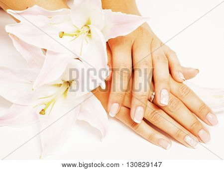 beauty delicate hands with manicure holding flower lily close up isolated on white, perfect shape concept