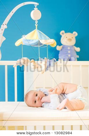Infant baby resting and playing in his little baby bed at nursery. Toys are officially property released.