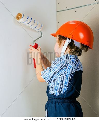 Four year old boy in protective helmet construction painstakingly paints the wall roller