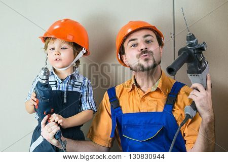 Satisfied dad with his little son doing home repairs