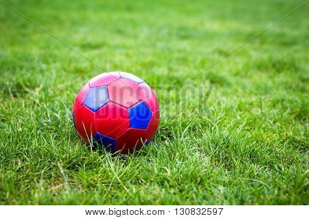 Red and blue fotball on green grass field