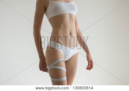 Fit young woman measuring her waistline grey blurred background with a space for your text
