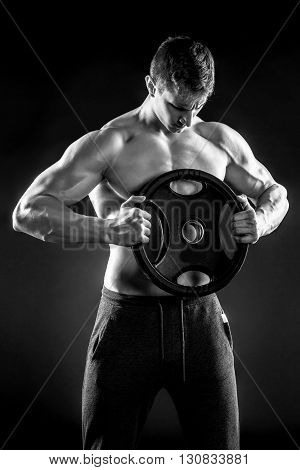 Mighty fitness man showing his gread body with dumbbells in hand on black background.. Black and white