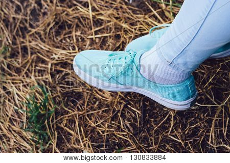 Female legs in sneakers and jeans on the background of dry grass in the Park